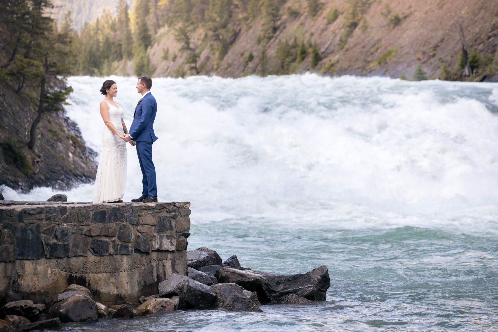 Bride and groom by a waterfall in Banff, Alberta