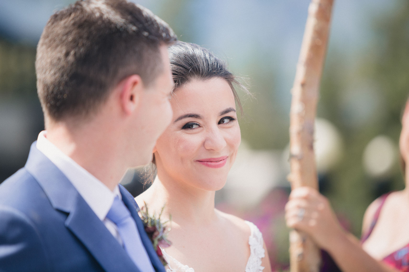 Bride and groom exchange a glance during wedding ceremony in Banff, Alberta, Canada.