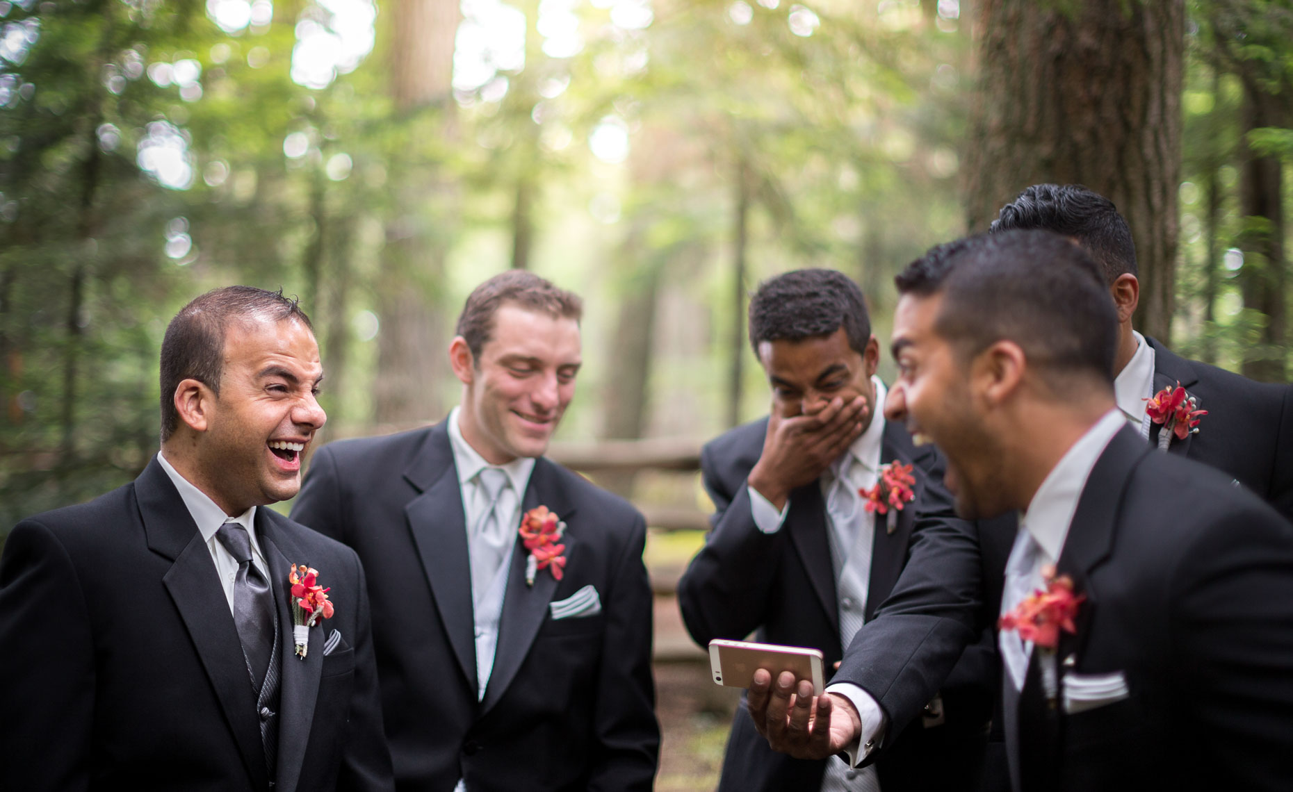 Groomsmen in the forest of Whistler BC laughing.