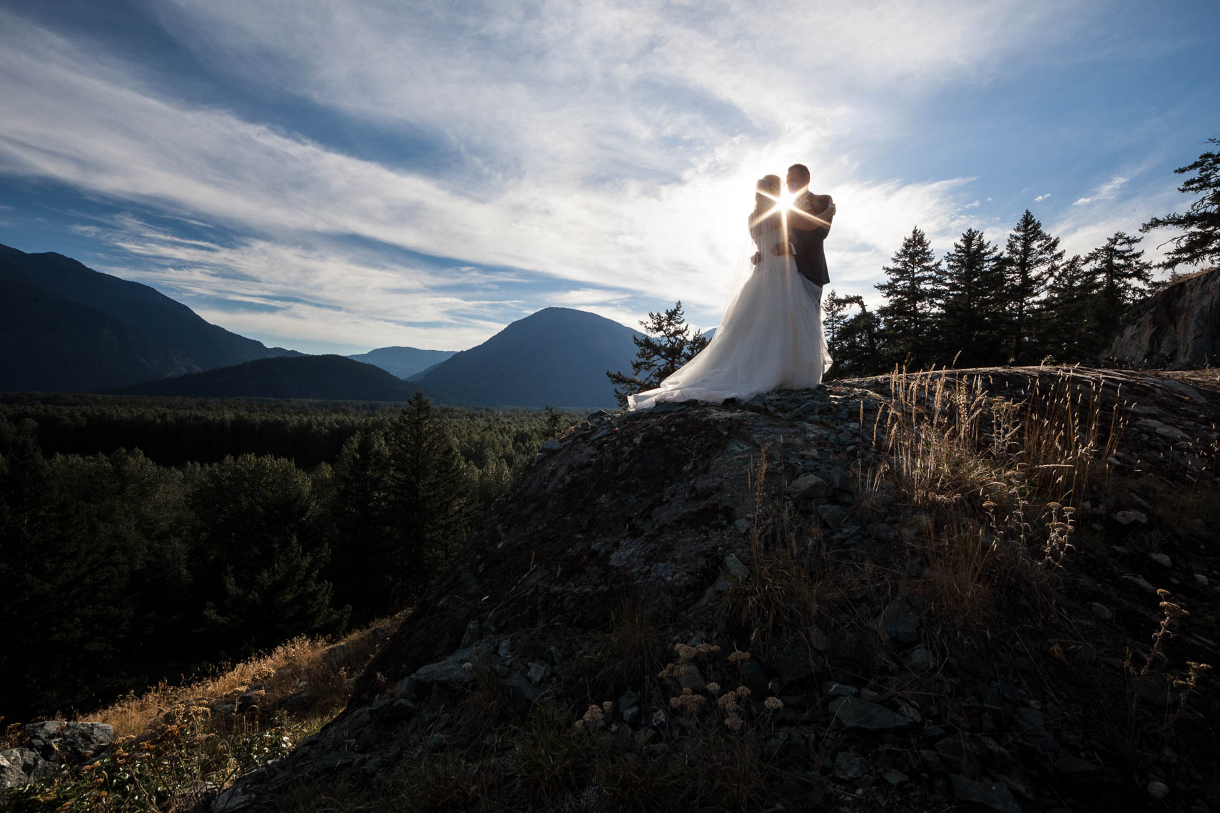 Sun flare silhouette of wedding couple in the mountains of Whistler BC