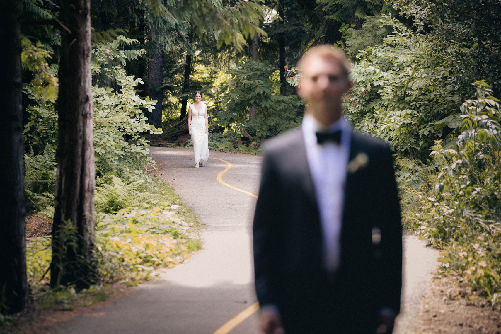 First look between bride and groom on a pathway in the forest of Whistler, BC.