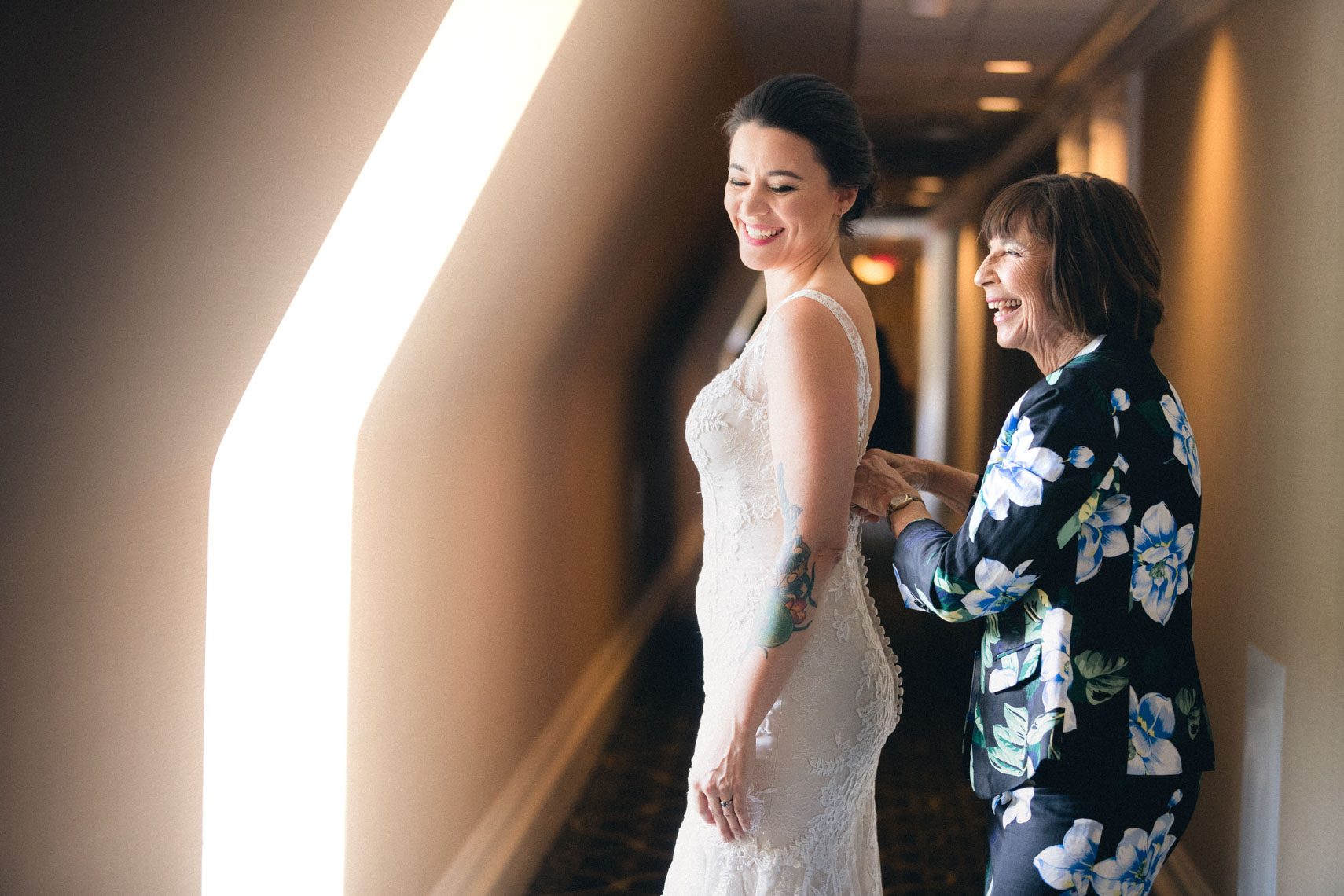Mother helps bride into wedding dress before ceremony at Banff Springs Hotel, AB