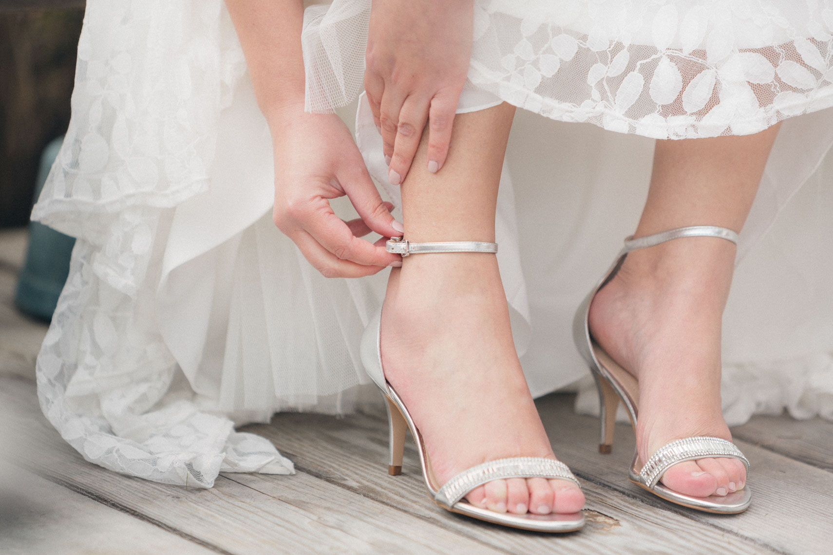 Closeup photo of bride fastening her wedding shoes