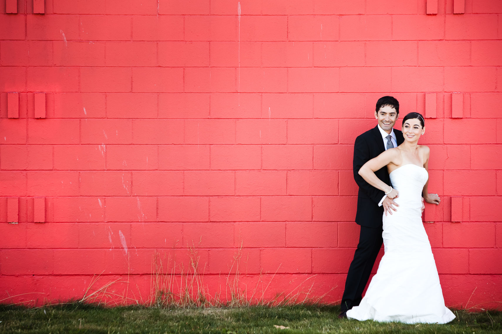 Bride and groom in front of a red wall in Vancouver BC.