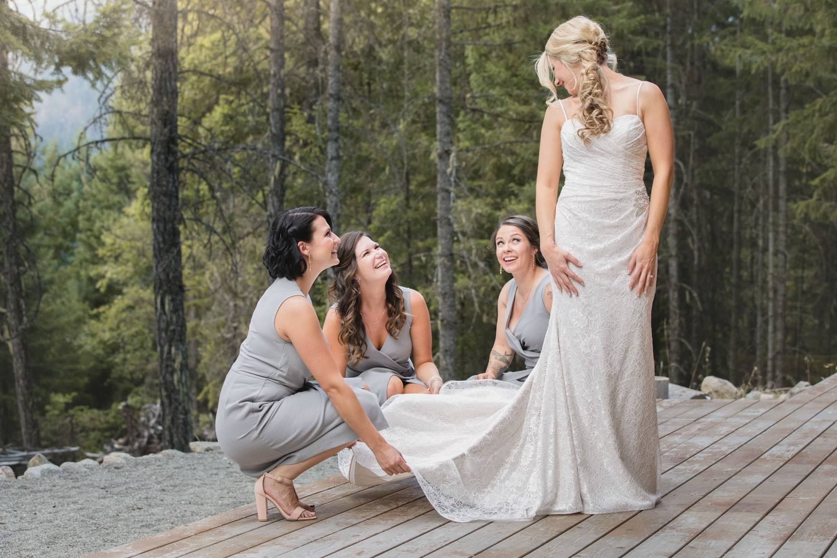 Whistler wedding photographer shows bridesmaids helping bride into wedding dress