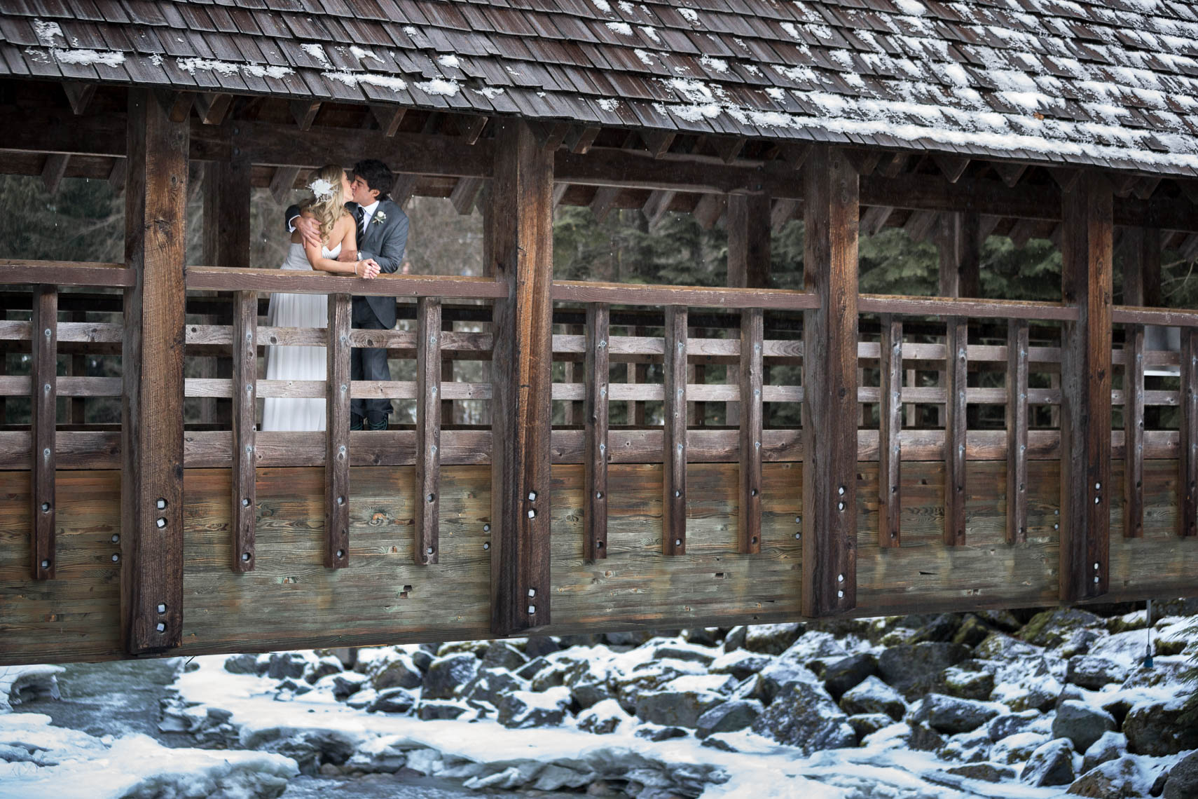Covered bridge in Whistler in the winter with bride and groom