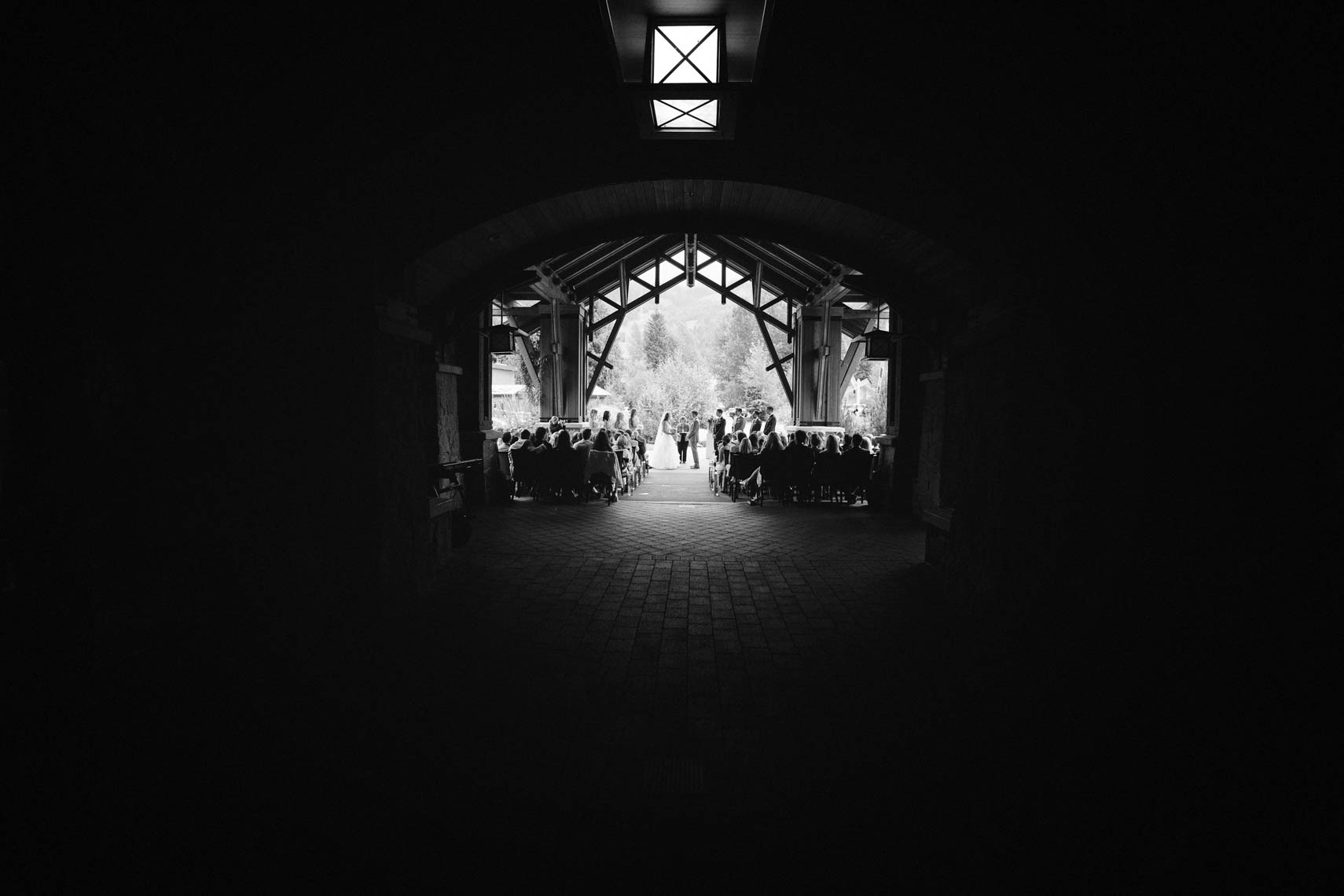 Wedding ceremony seen through tunnel at Nita Lake Lodge venue