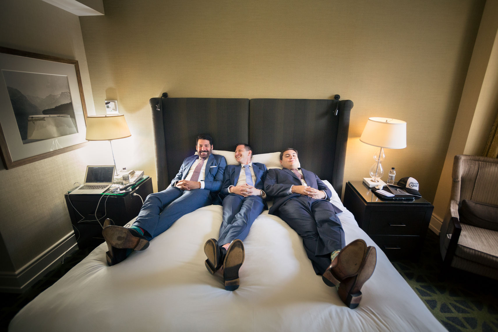 Groomsmen relax on a bed in Banff Springs Hotel Alberta