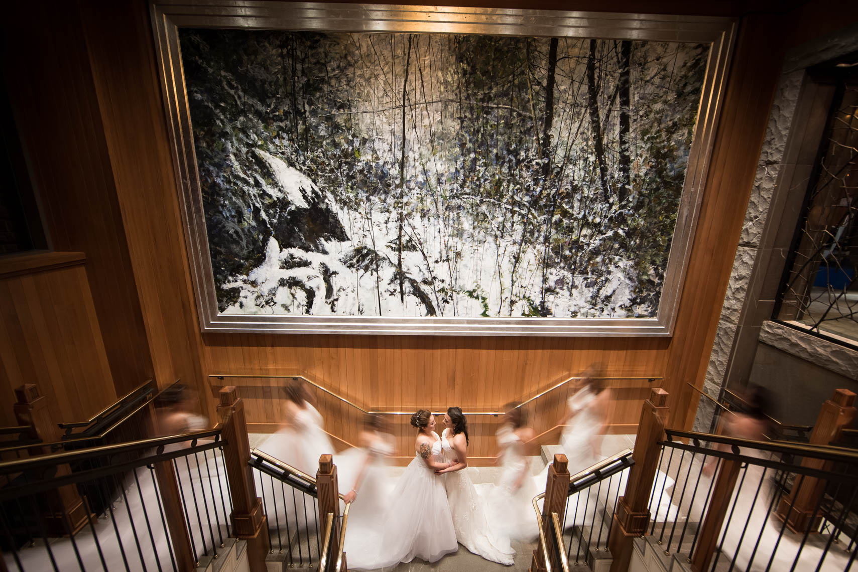 Two brides under a large painting at whistler luxury hotel venue
