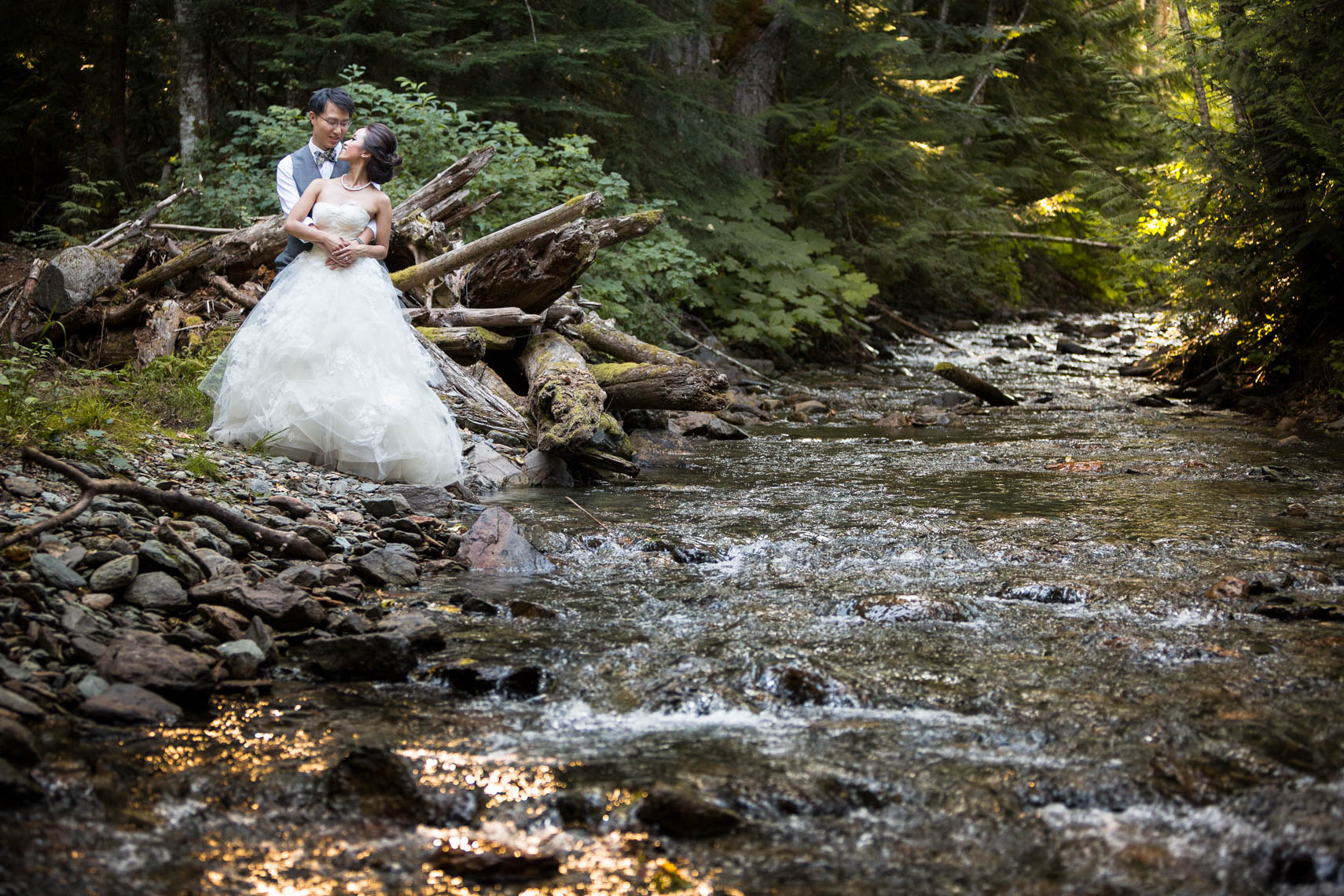 Bride and groom embrace near a woodland stream in Whistler, Canada