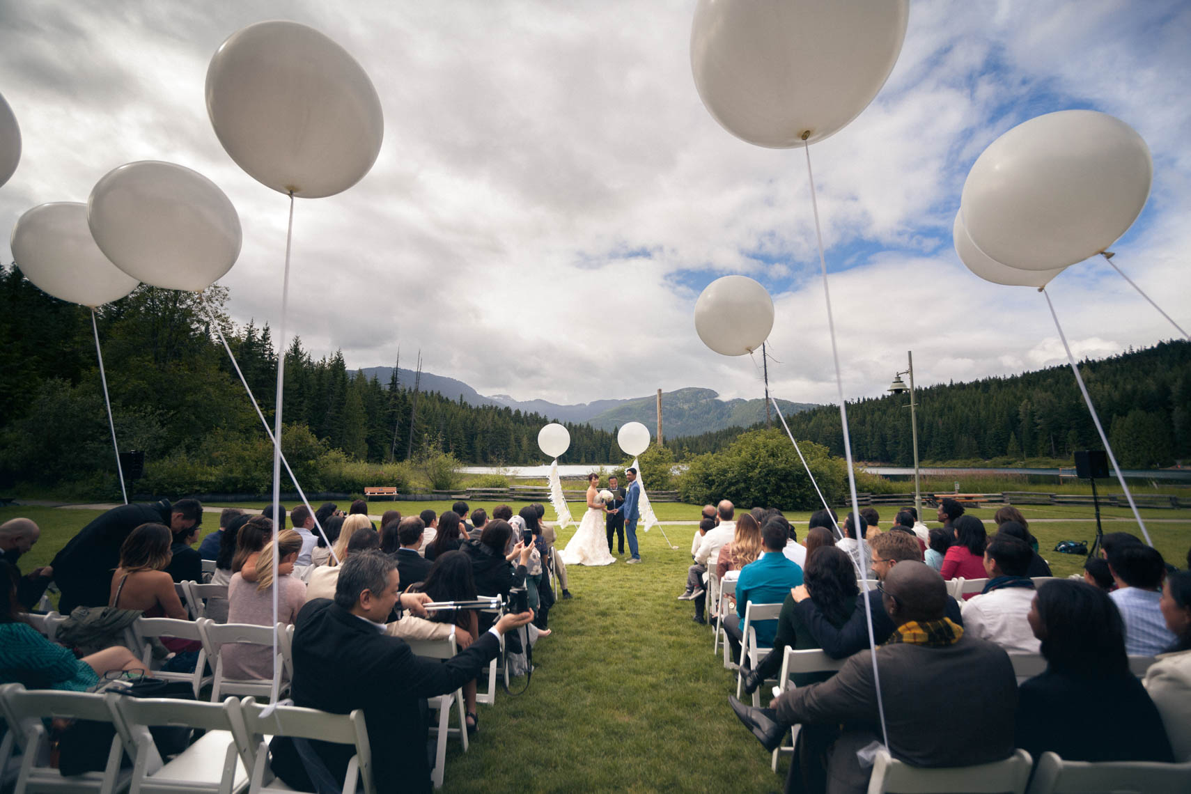 Wedding ceremony with large round balloons near rainbow lake in Whistler