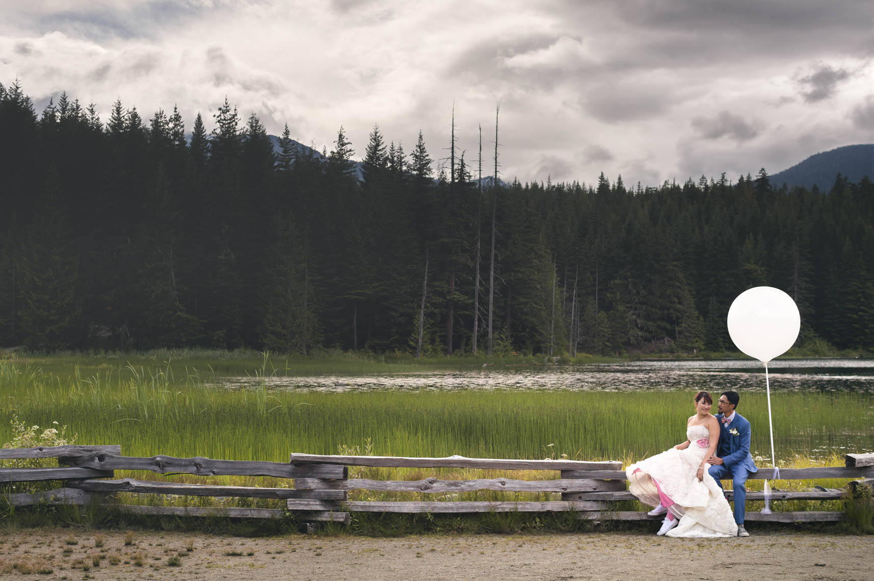 Bride and groom sit on a wooden fence near forest and lake in Whistler