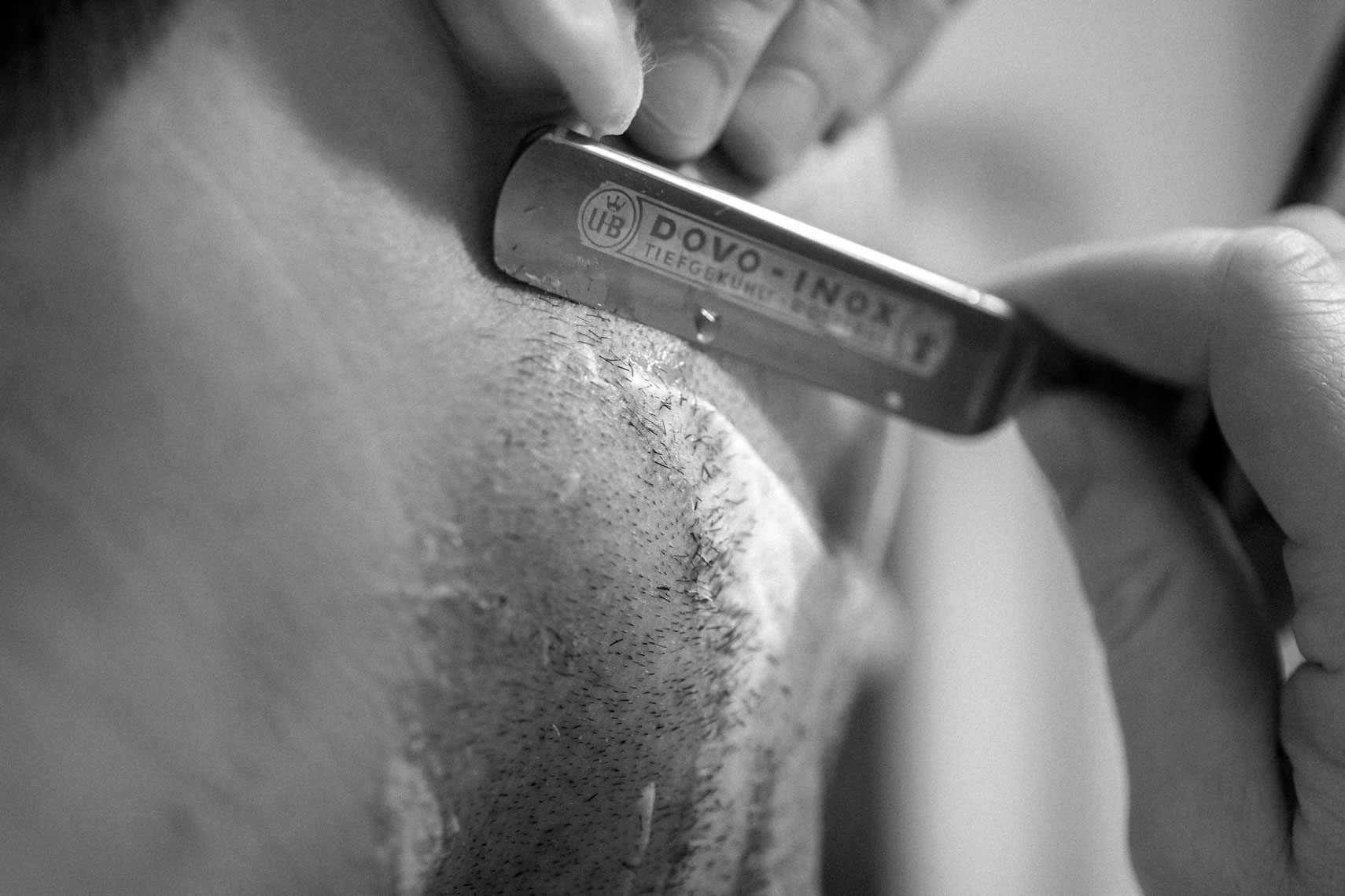 Groom shaving with a straight razor before the wedding
