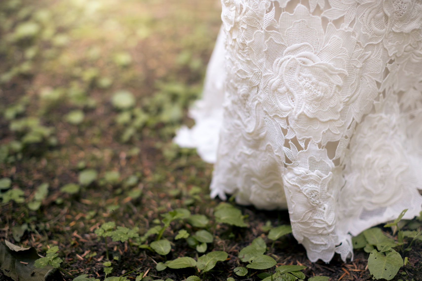 Wedding dress hem detail in the forest