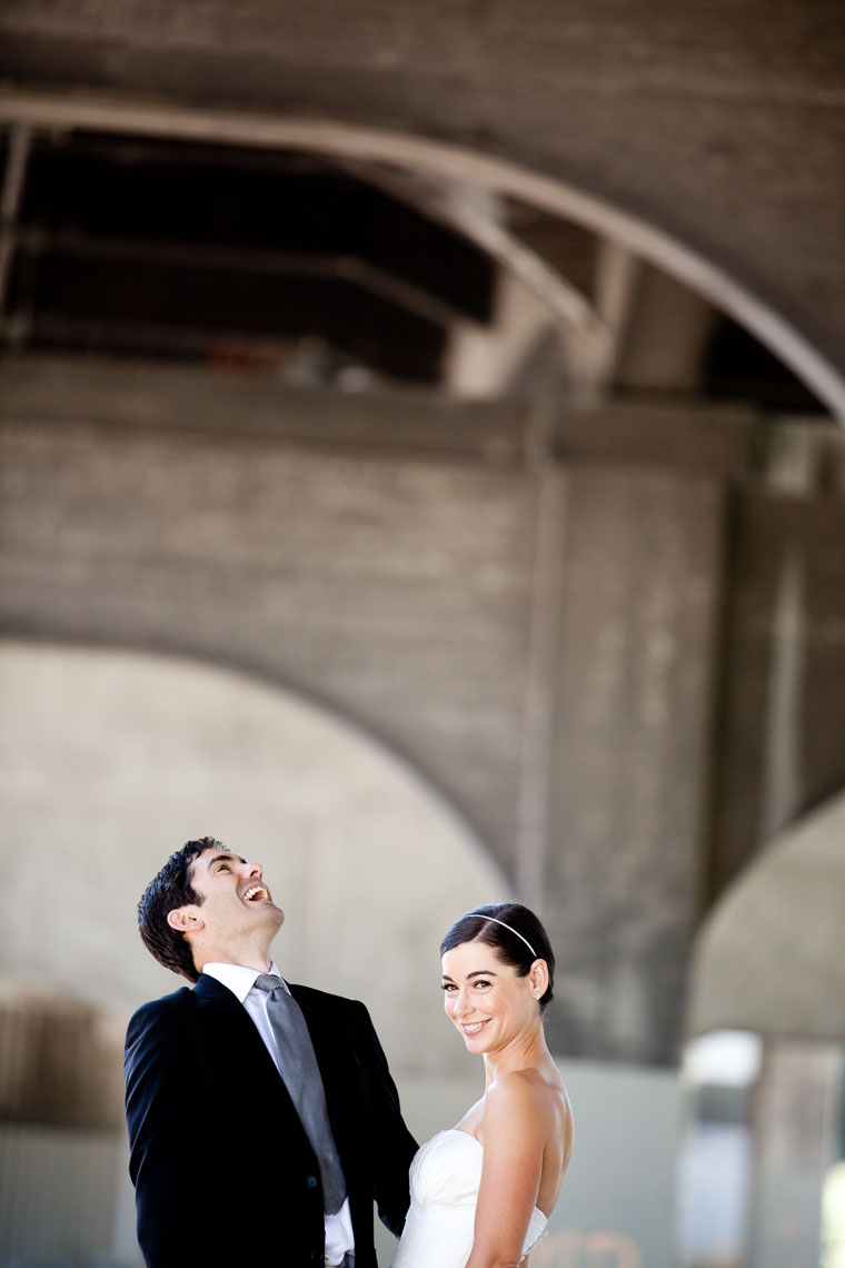 Bride and groom laugh under the Burrard bridge before Vancouver wedding