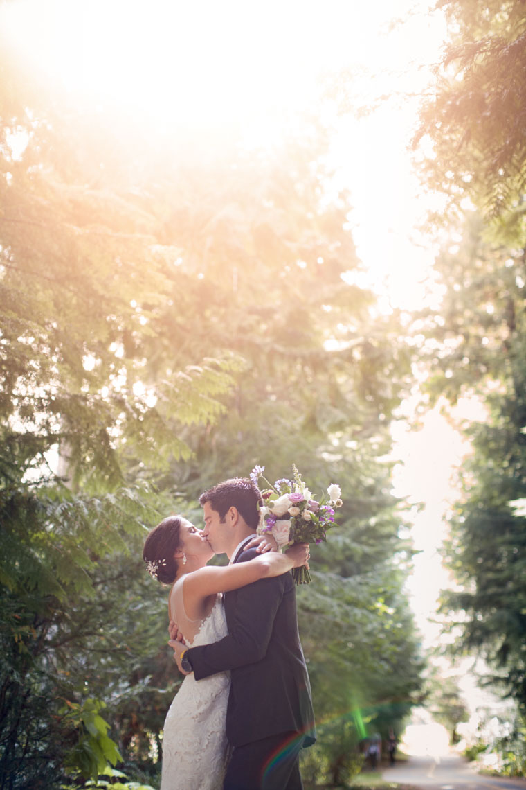 Bride and groom kissing with sun flare by whistler and vancouver wedding photographer