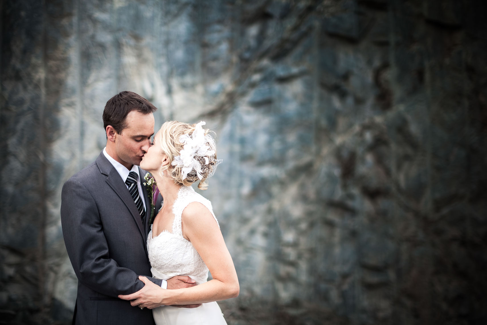 Bride and groom kiss in front of rock wall before ceremony at big sky golf wedding venue in Pemberton BC near Whistler