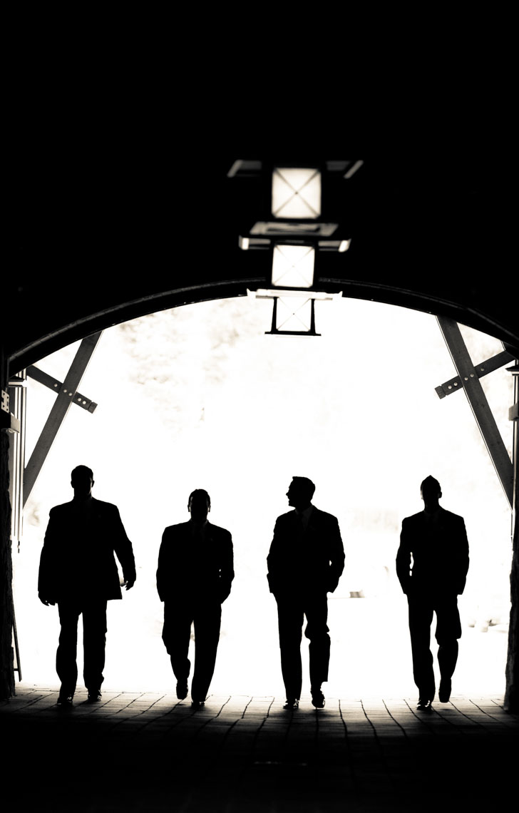Silhouette of groomsmen walking through tunnel at Nita Lake Lodge wedding venue