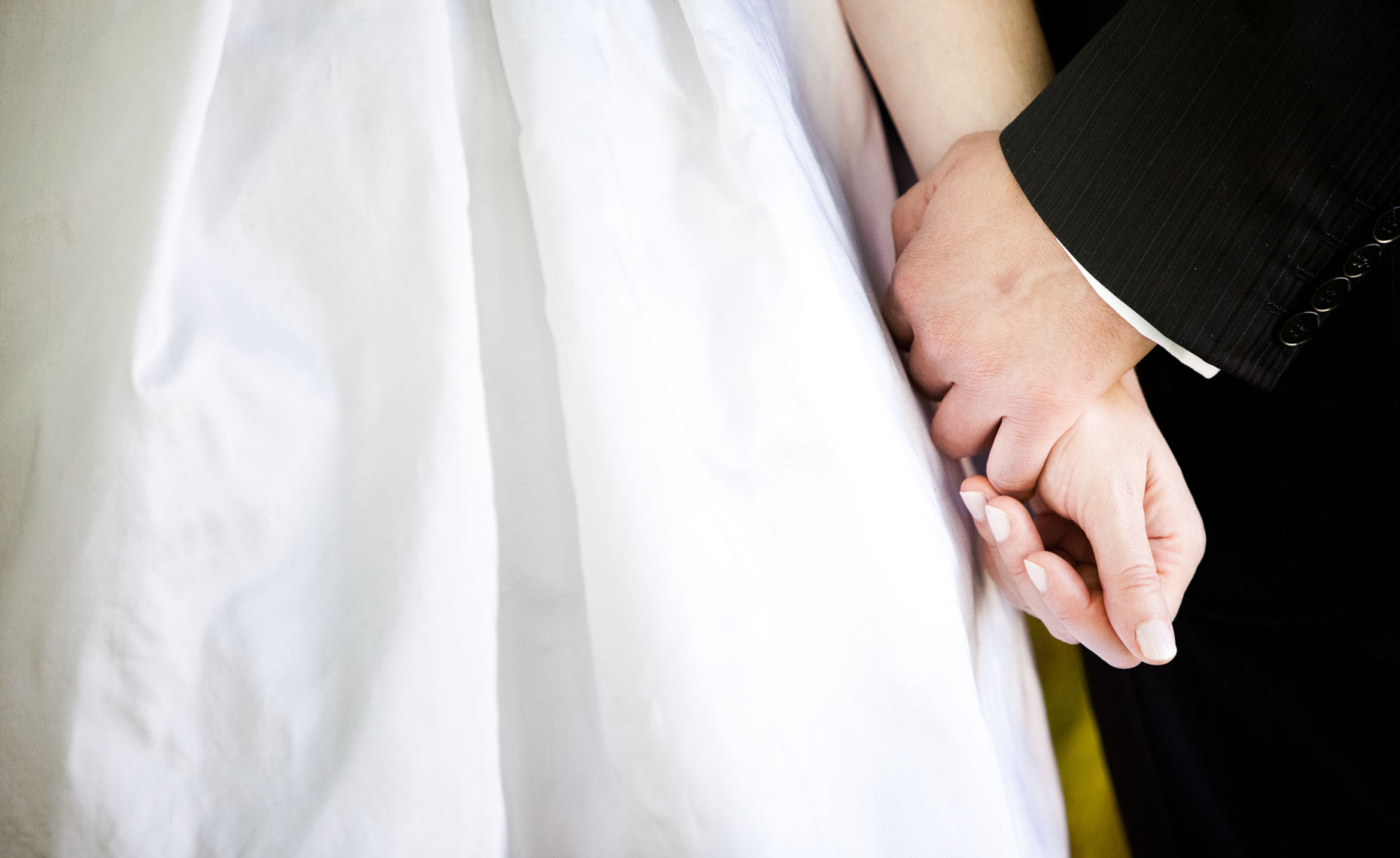 Closeup of bride and groom holding hands during wedding in Whistler, BC