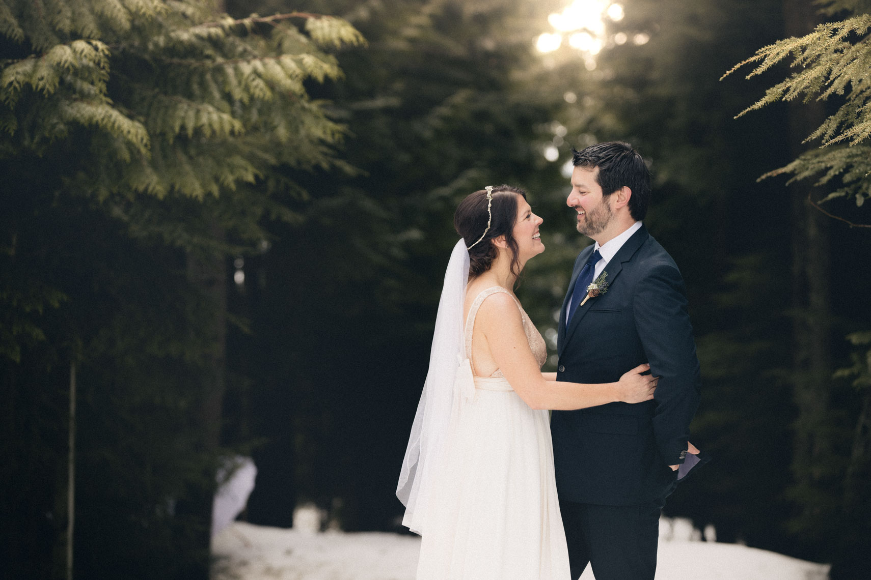 Bride and groom on a snowy forest path in Whistler before the ceremony