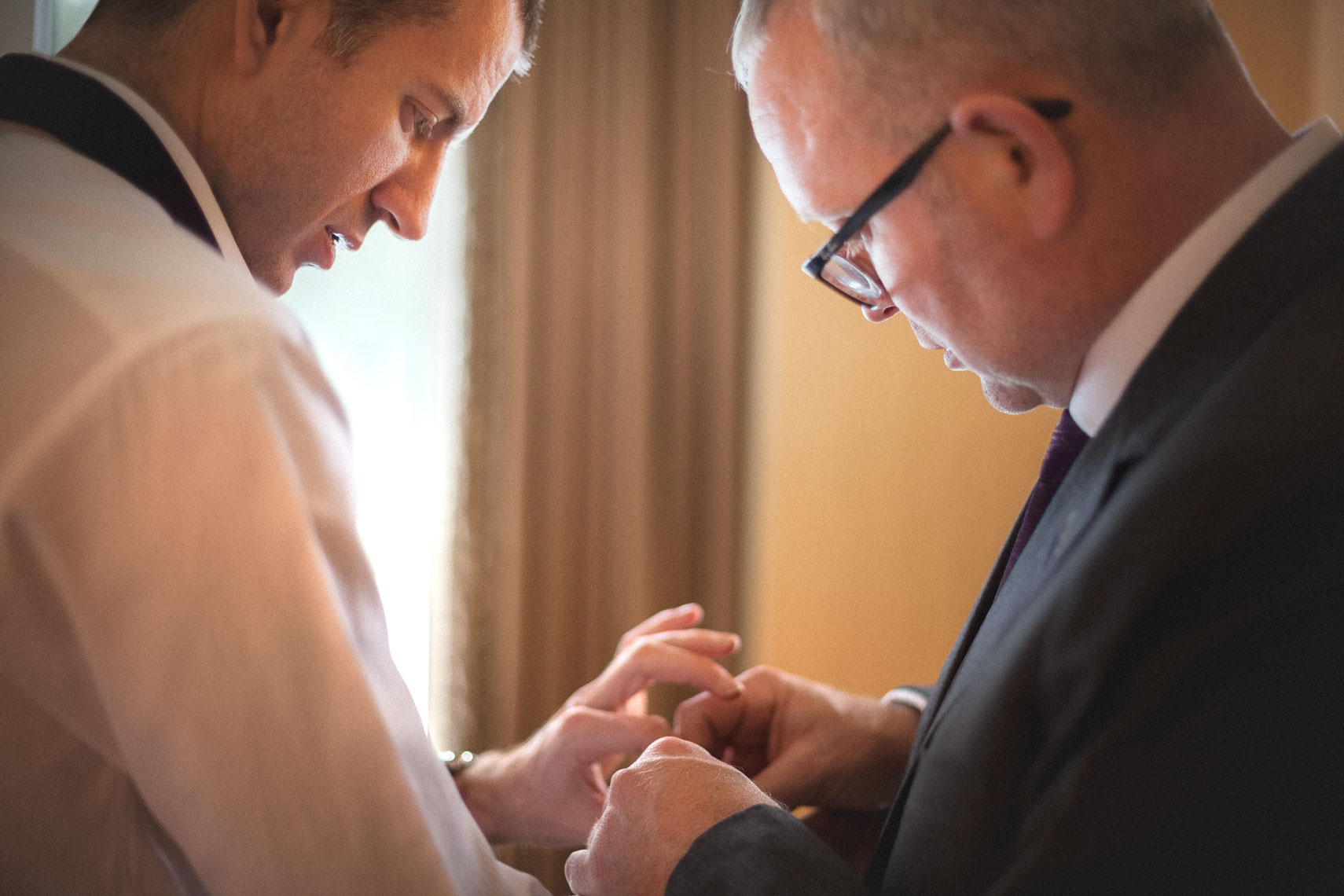 Groomsman helps groom with cufflinks before wedding ceremony in Whistler, BC
