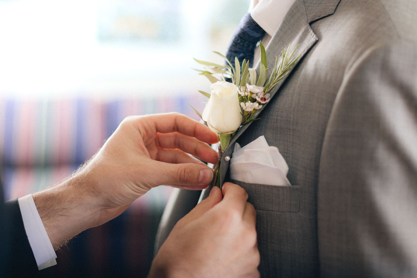 Groom gets boutonniere pinned on during wedding in Whistler