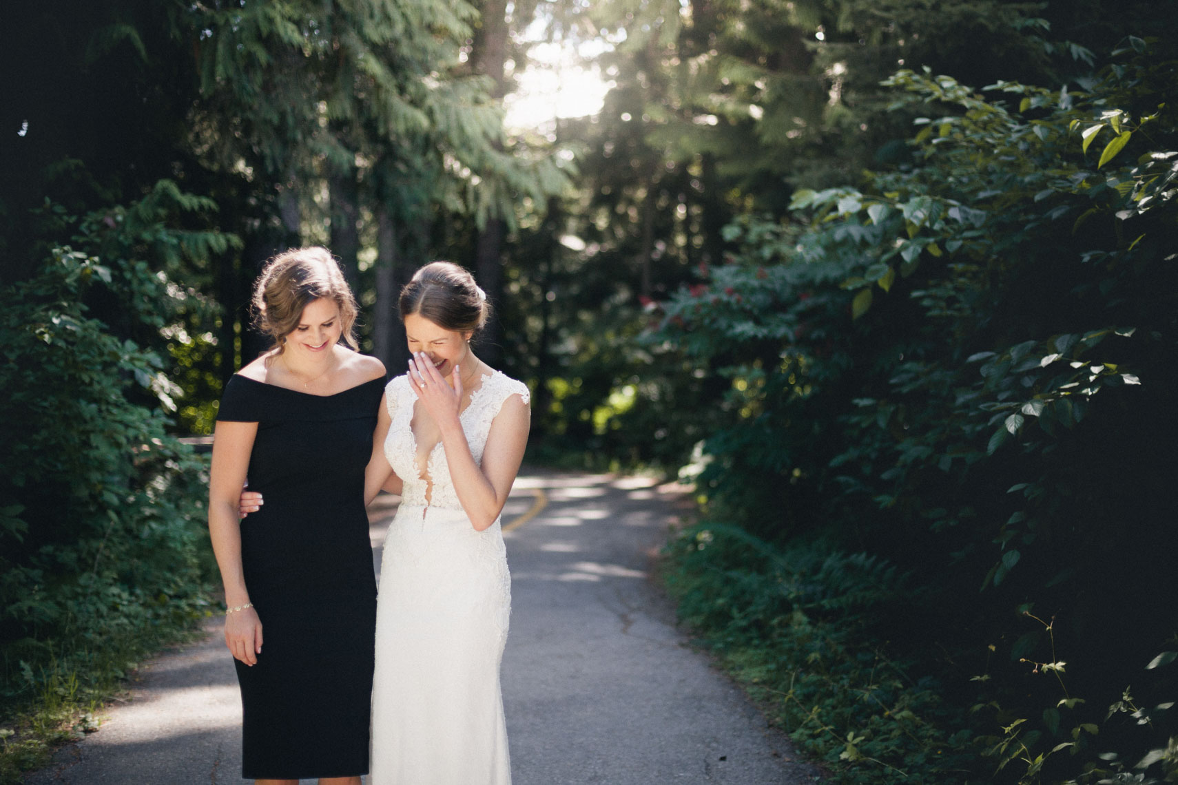 Bride and bridesmaid share a candid moment in the forest of Whistler BC
