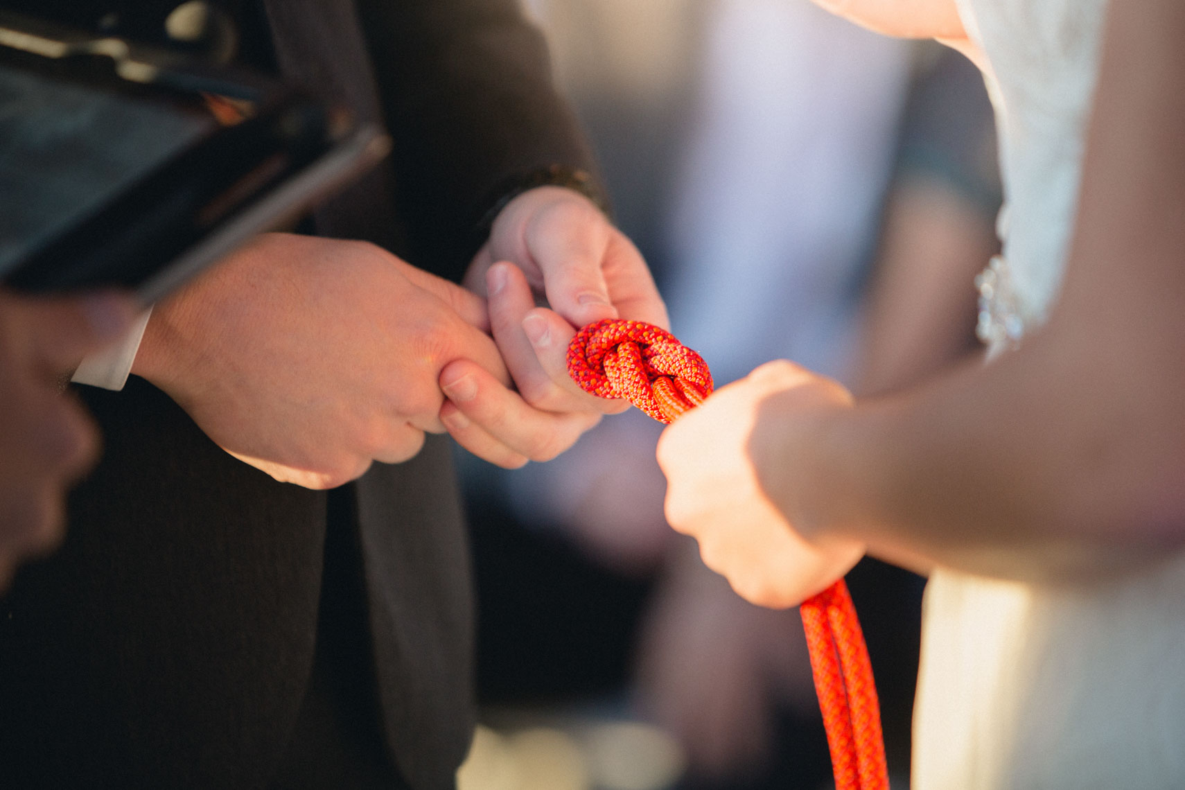 Bride and groom holding symbolic rope during ceremony