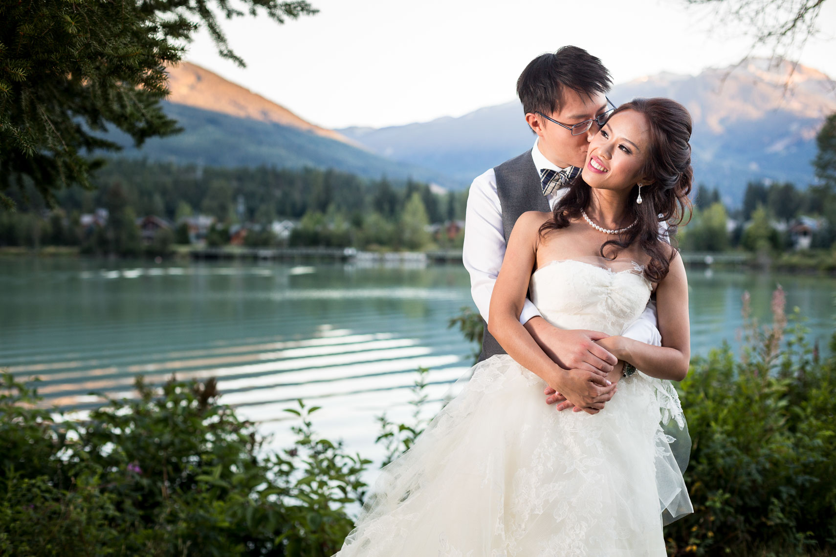 Bride and groom embrace near lake at nicklaus north wedding venue in Whistler