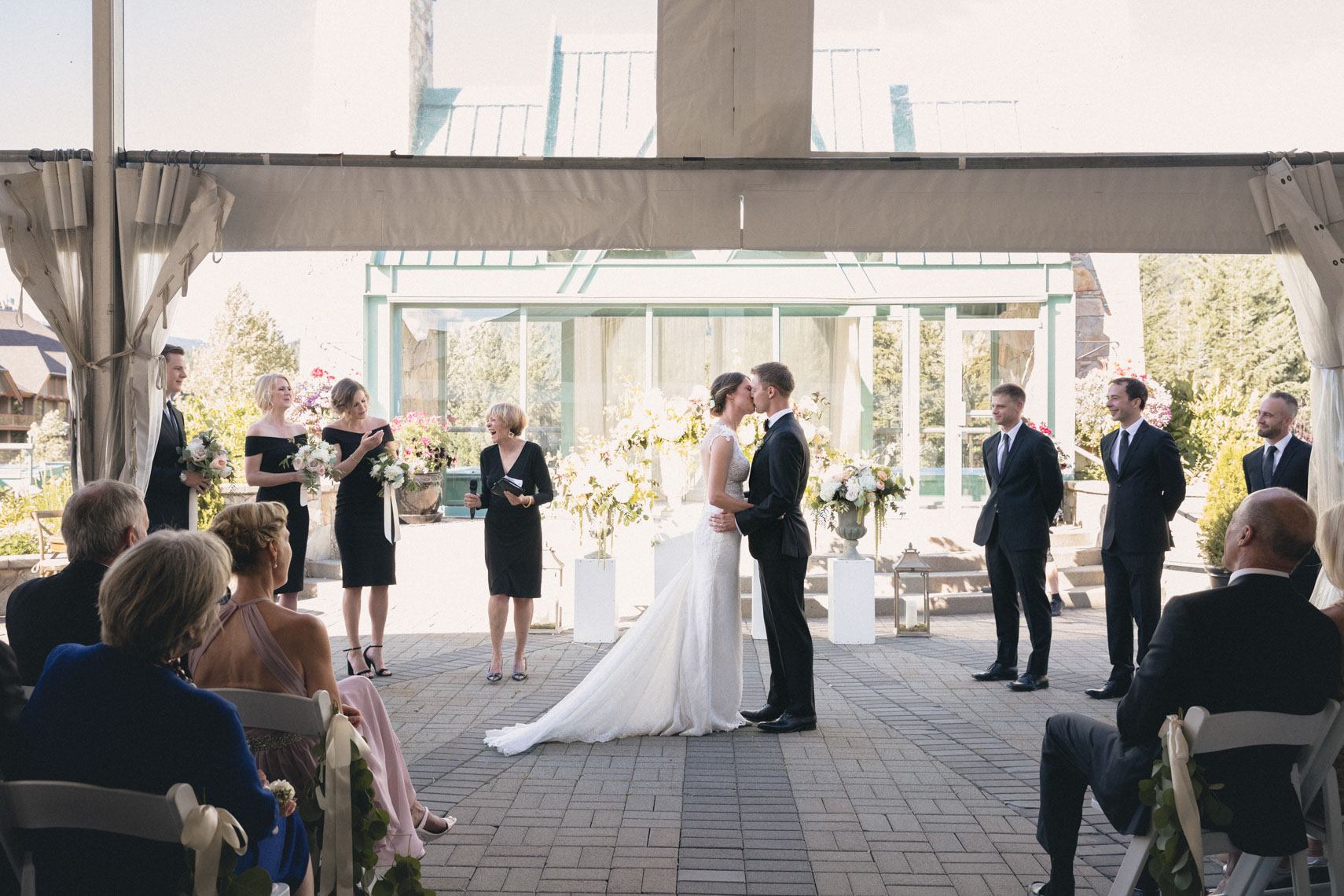 First kiss between bride at groom at rooftop ceremony in Whistler, BC