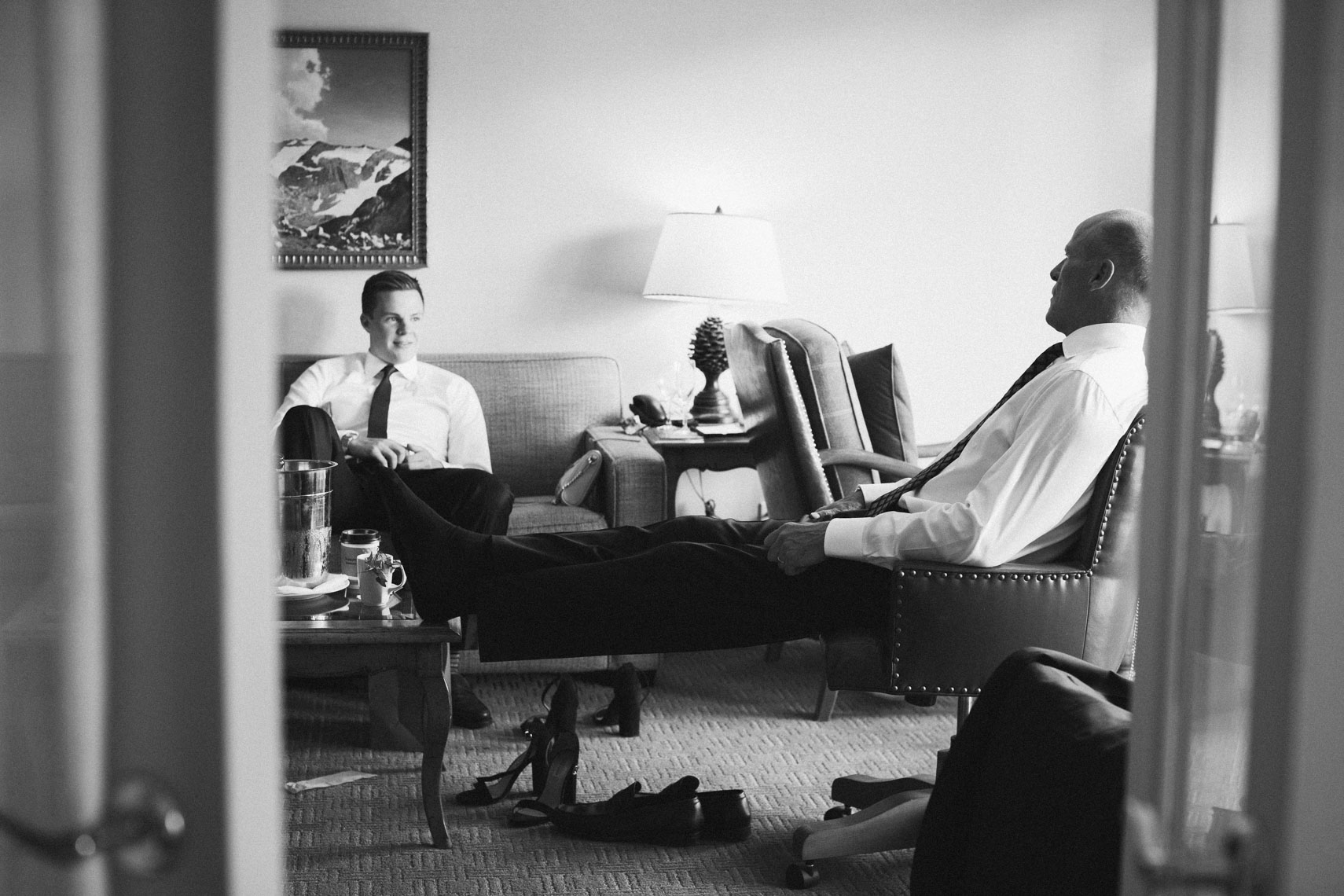 Photojournalist style wedding photography of father of bride with groomsman in hotel room before wedding