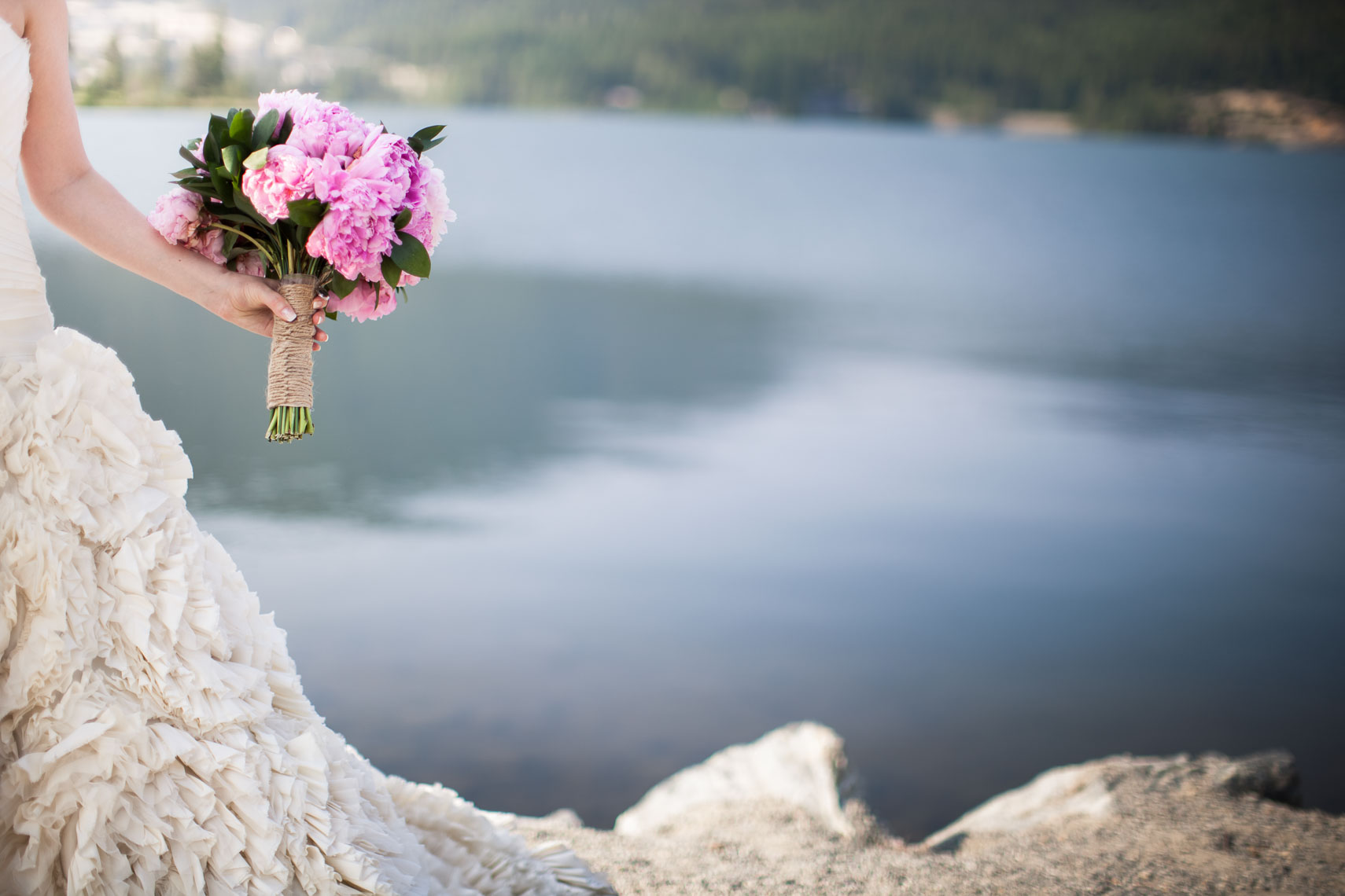 Bride holding wedding bouquet by Lost Lake in Whistler BC