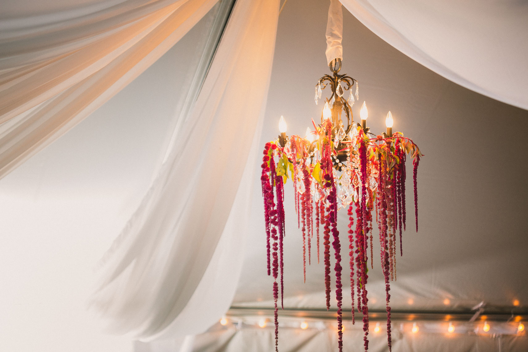 Chandelier with floral decoration in tent at nicklaus north wedding venue