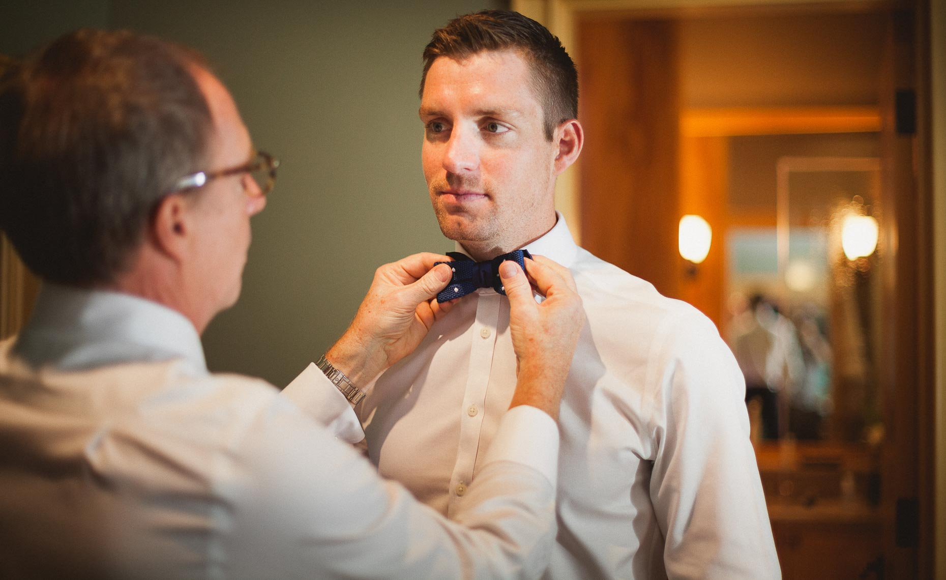 Groom and father getting ready before outdoor wedding ceremony in Whistler, BC