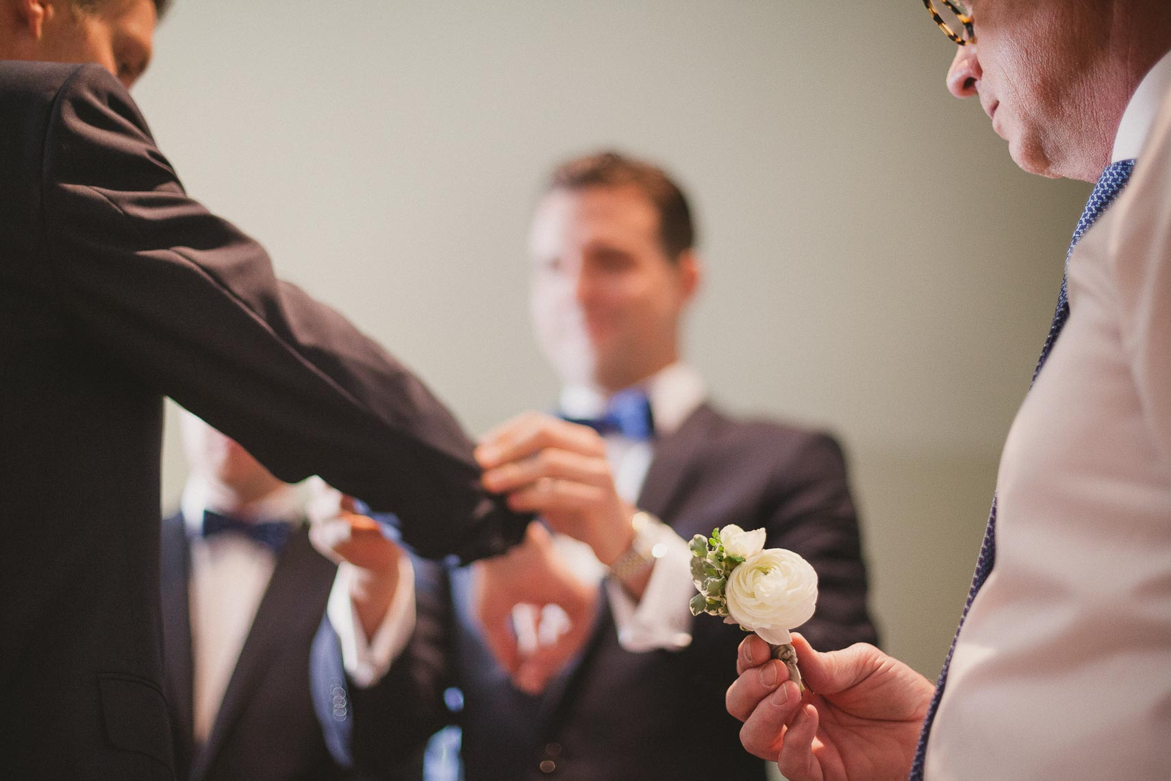 Groom with groomsmen and father pinning boutonniere