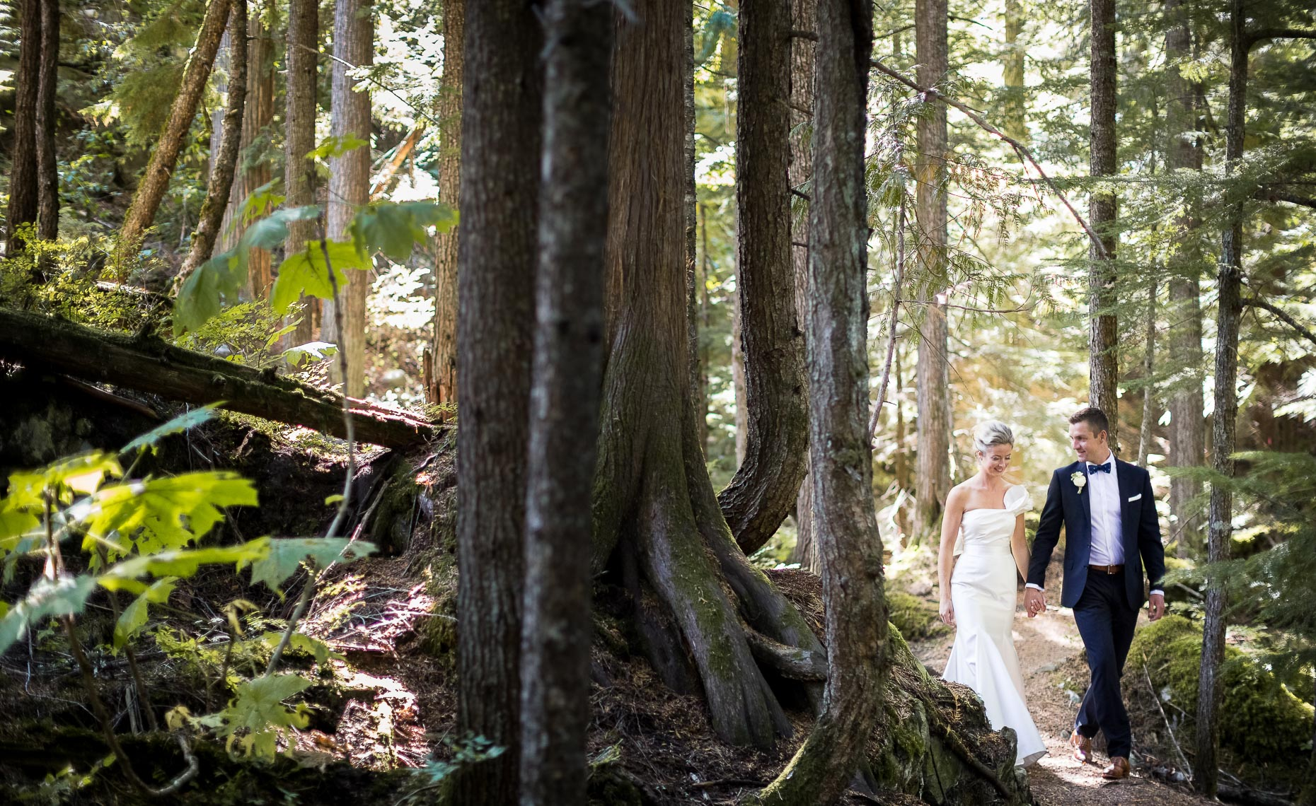 Wedding couple walking in the forest wilderness of Whistler