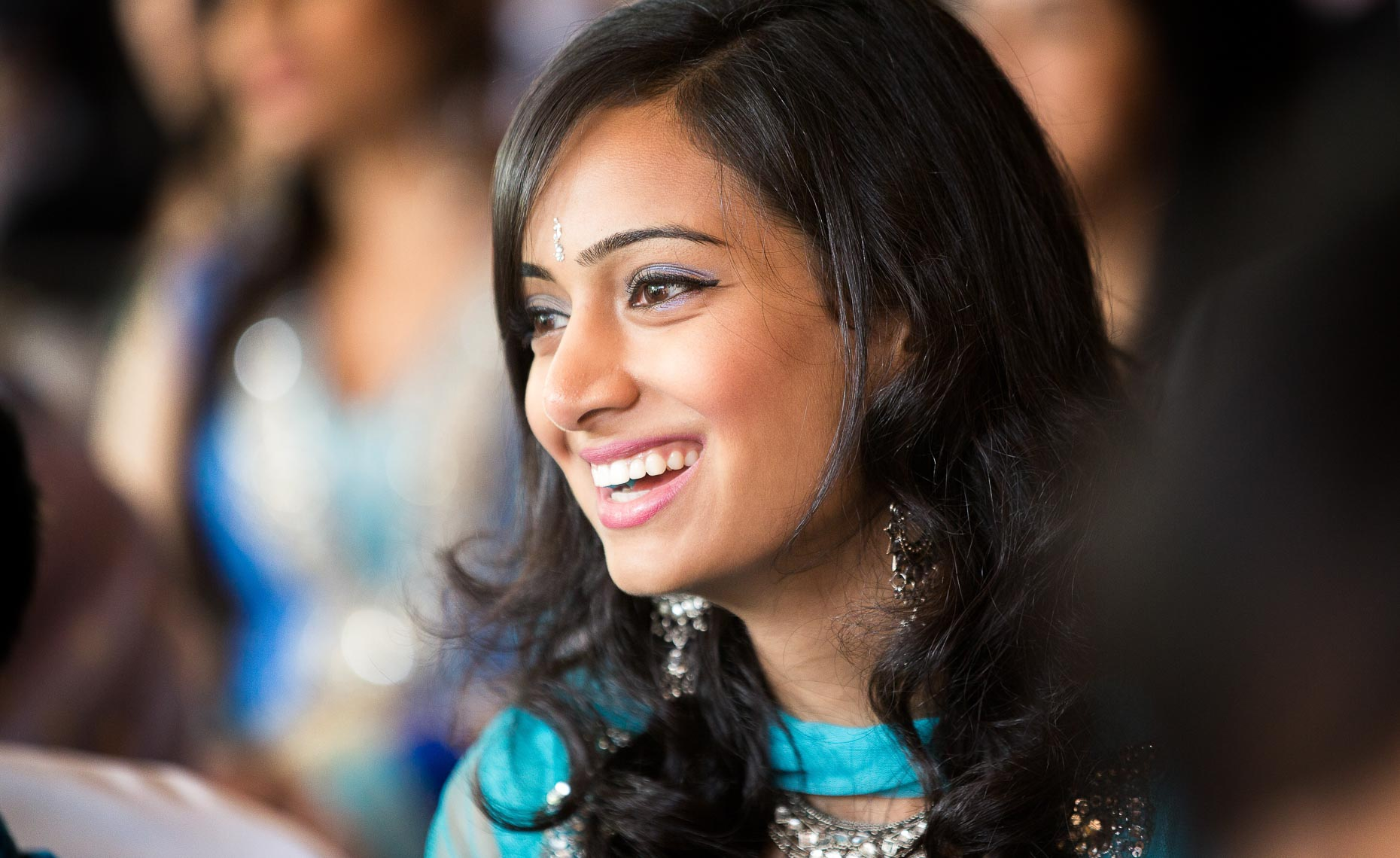Indian wedding guest laughs during ceremony in candid moment