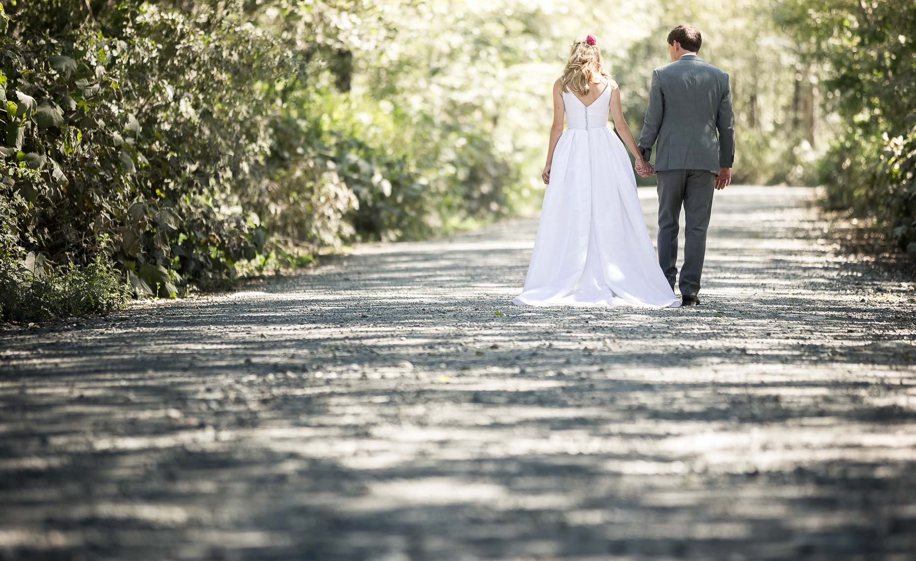 Bride and groom walk together at sunny whistler summer wedding