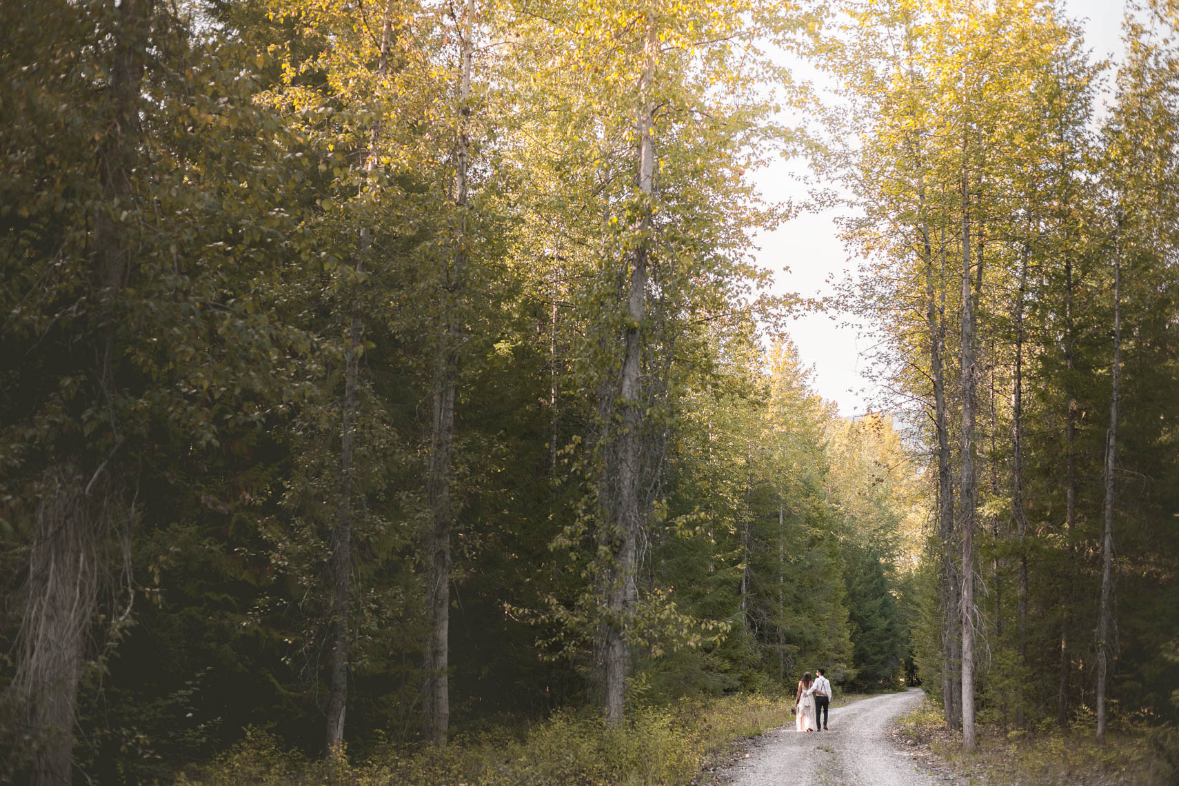 Bride and groom on a forest path after their vintage-style farm wedding