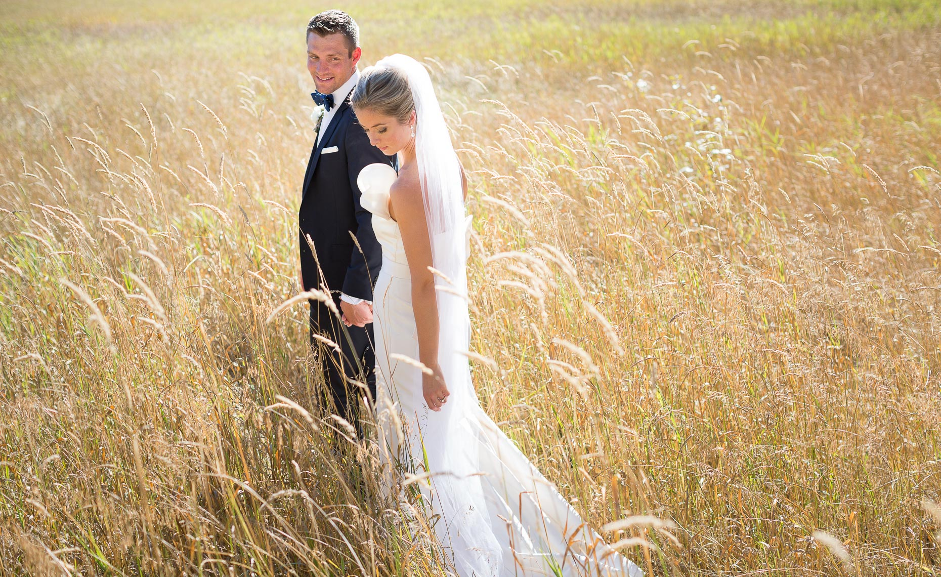 Stylish wedding couple walk in a field in Whistler summer wedding