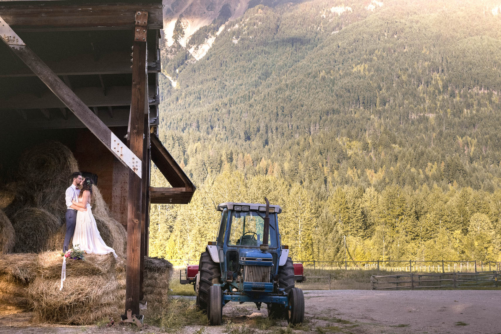 Bride and groom on bales of hay near a tractor during farm wedding