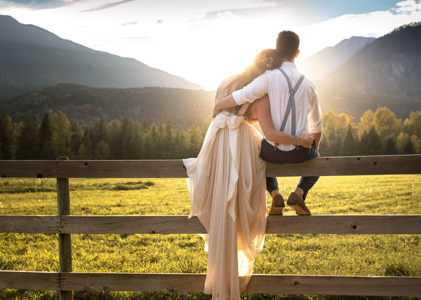 Bride and groom on a wooden fence at sunset in the mountains.
