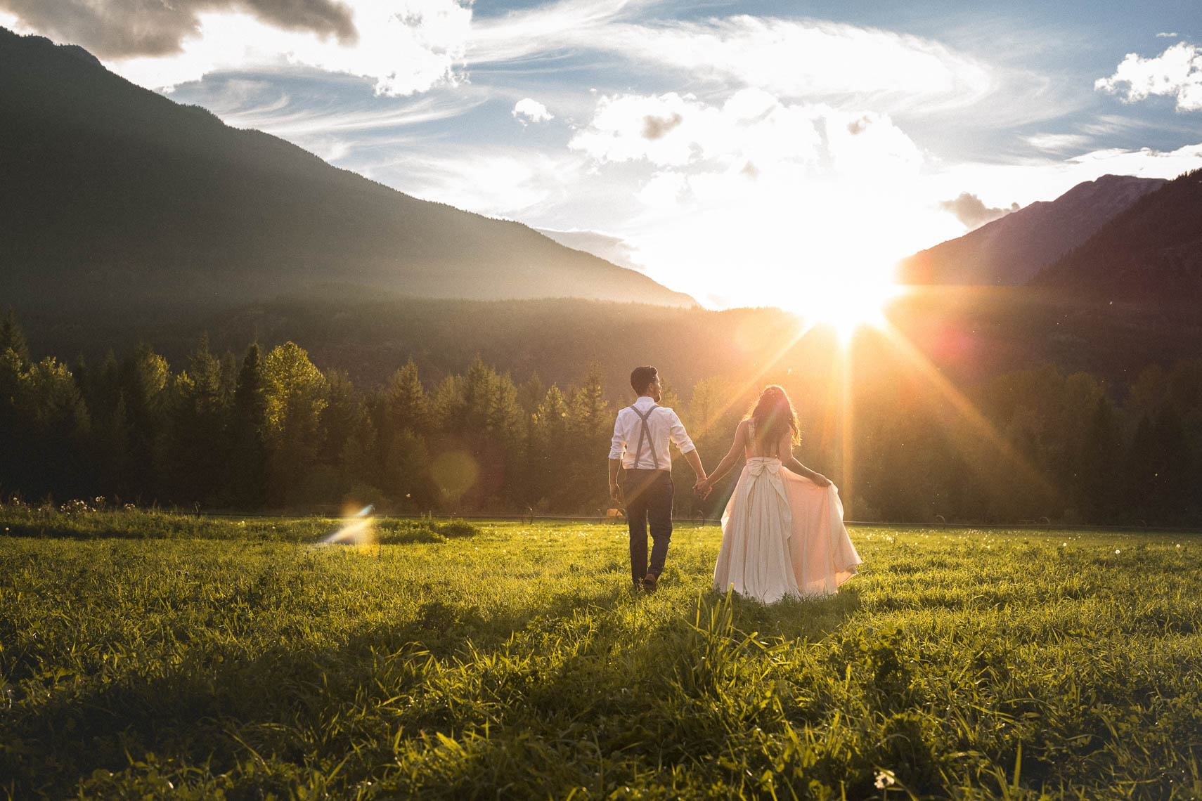 Bride and groom walk in a field after rustic vintage style wedding near Whistler, BC.