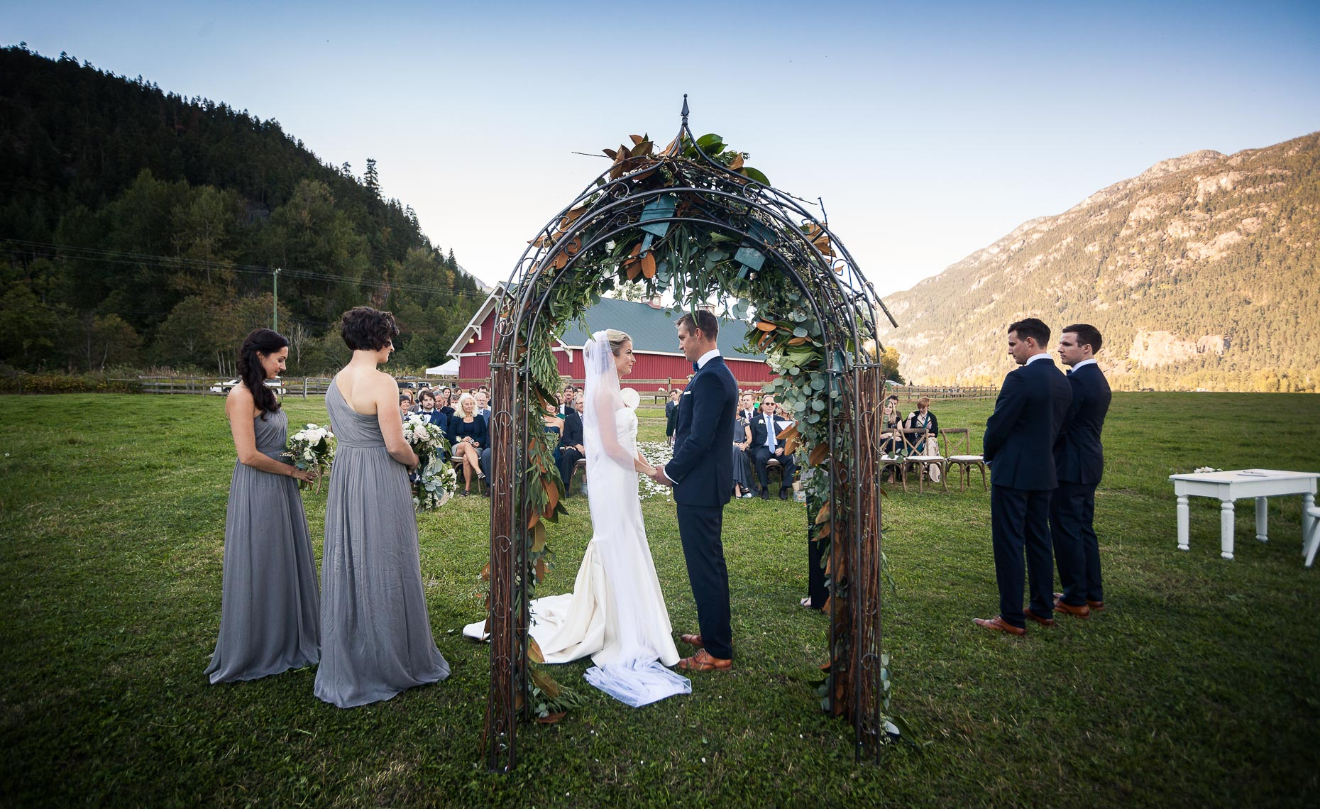 Bride and groom under wedding arch during whistler farm ceremony