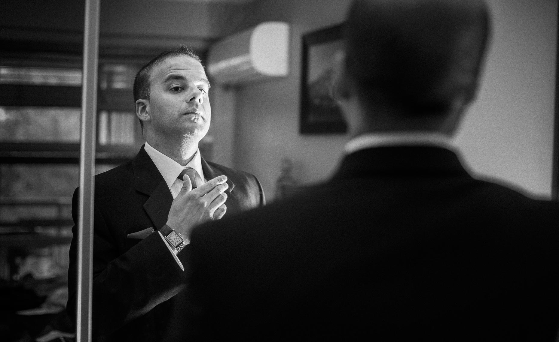 Moody wedding photography of groom getting ready