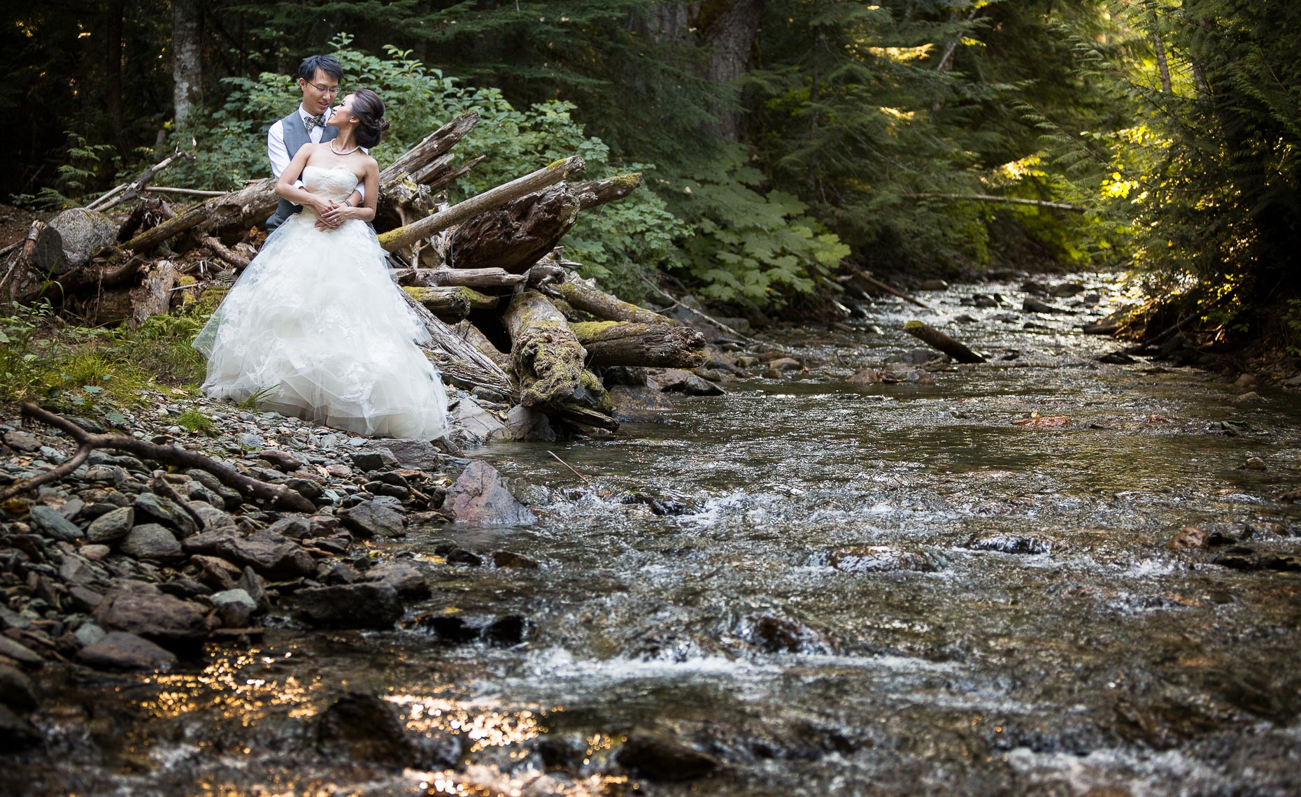 romantic wedding photographer portrait by a stream in whistler