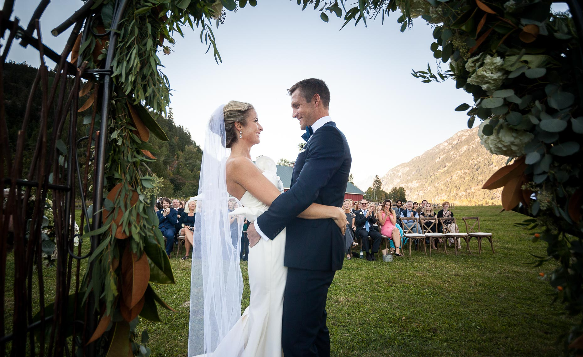 Couple beneath wedding arch in scenic summer wedding in pemberton