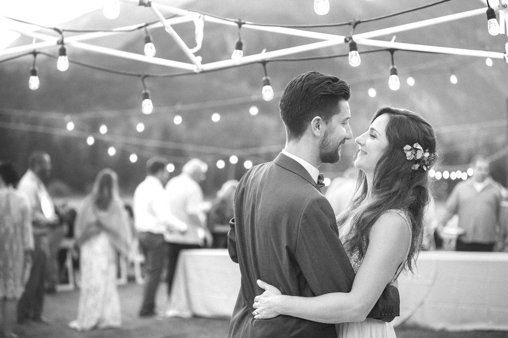 Black and white bride and groom dancing outdoors under tiki lights