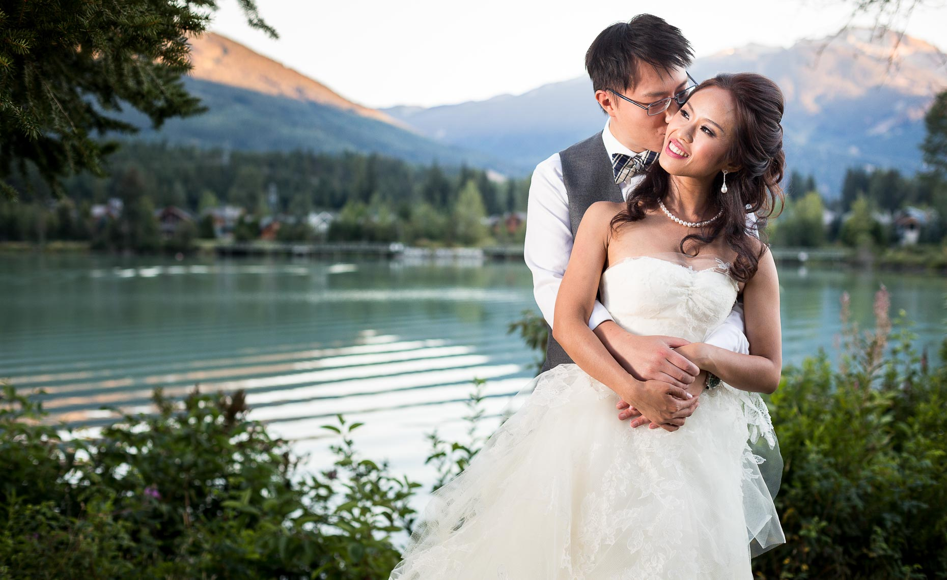 Whistler wedding couple in intimate moment portrait with lake and mountains
