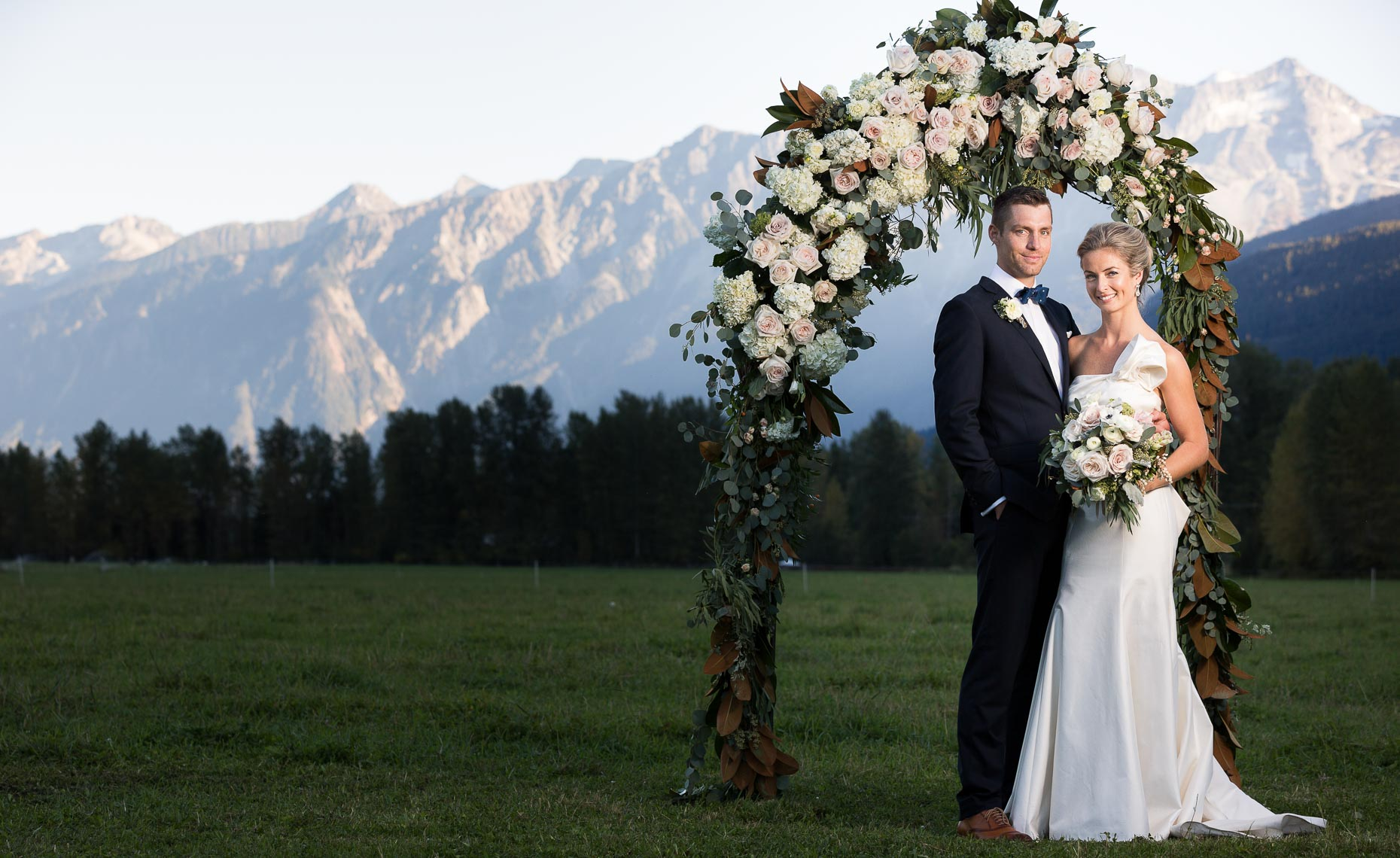 Bride and groom under the wedding archway in front of mountains in pemberton